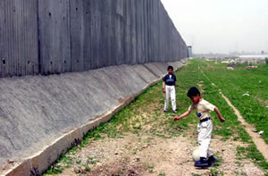 two children playing on the grass next to a giant wall