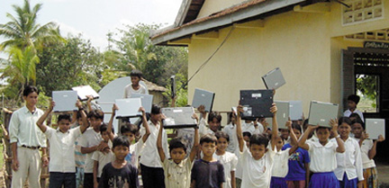 kids outside holding laptops over their heads